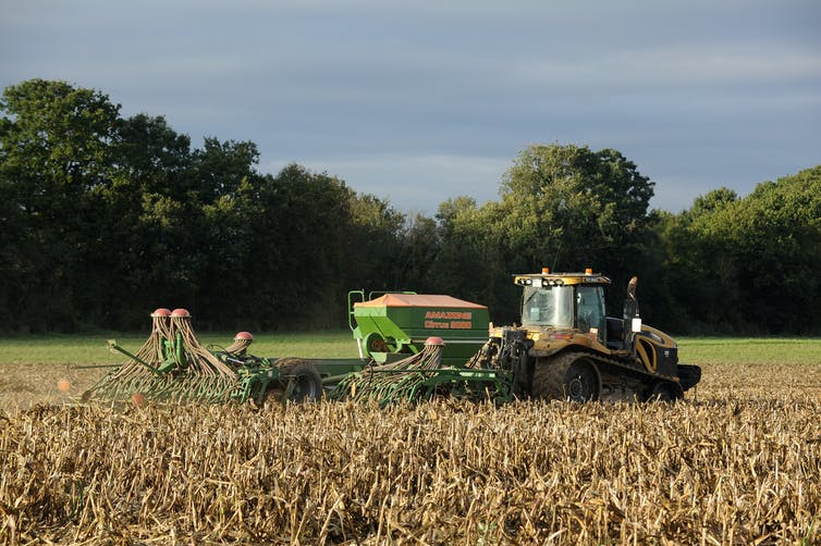 Un tracteur avec un semoir mécanisé en remorque prépare un champ pour l'ensemencement