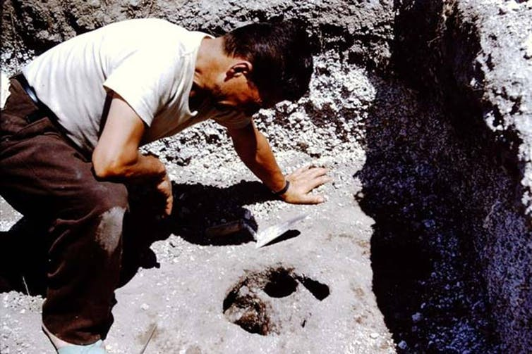 An old photograph, a man leans over a hole in the dirt